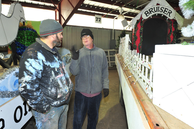 "Michael Young, left, listens to concerns of Paul Aiken, the artist behind Estes Park's favorite rag dog, at Barn ""W"" on Monday. Young collaberates with public works employees and other artists in constructing the floats for the annual Catch the Glow Parade."