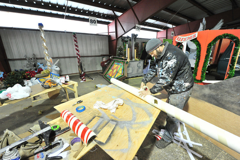 "Artist and float builder Michael Young builds components for floats at Barn ""W"" at the Stanley Fairgrounds on Monday. Young and the town are working furiously to complete the Catch the Glow Parade floats, as they, too, were set back by September's flood."