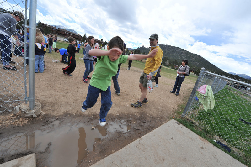 First-grade student Logan Frame bounds over a puddle at the Estes Park Elementary School on Wednesday. Melting snow and rain have created obstacles, but imagination has created adventure in the puddles.