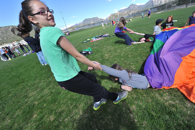 Brenda Luna pulls classmate Meghan Frey from a whimsical shark attack at the Stanley Faorgrounds on Wenesday. The game was one of many at the school-year-ending elementary school field day.