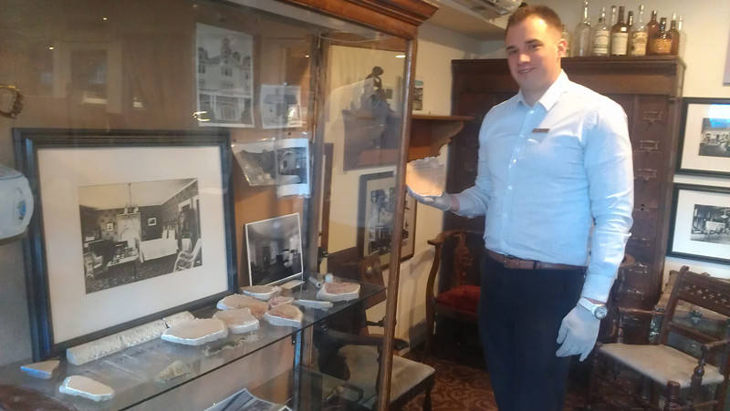 Jesse Frietas stands by the case which hold the debris from the 1911 explosion in the Stanley Hotel's Archive Room.