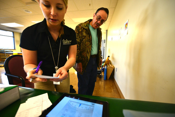 Sarah Senton, third-year physical therapy assistant intern, analyzes numbers like weight, height and body fat percentage to give a health fair visitor something he can use. Determinig a healthy weight goes well beyond numbers on a scale and now requires a lot more technology.