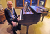 Walker sits at his piano in his home on Monday. Walker played and taught cello for many years, but first learned and composed music on the piano.