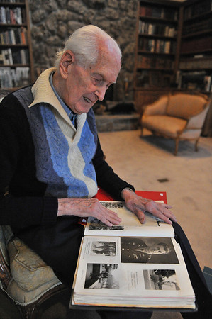 Walker shows photos of himself and other soldiers from the Second World War. Walker served in the infantry during the Normandy invasion in 1944.