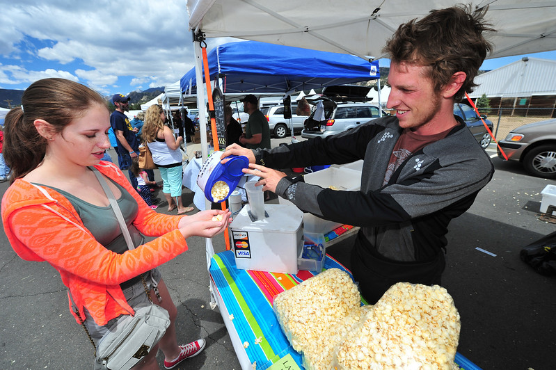 Madison Clark, 17, of Lincoln, Nebr., enjoys a sample of Heaven's Popcorn from Lindon Hunter of Loveland on Thursday. The market attracts visitors from far and wide.