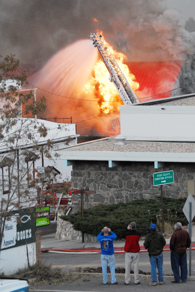 21EP View Citizen Documentarians.jpg Photo by Walt Hester<br /> Estes Park residents snap shots of the growing fire in the Park Theater Mall on Monday. Firefighters were not able to enter the mall, due to it's structure, so they could only contain the fire.