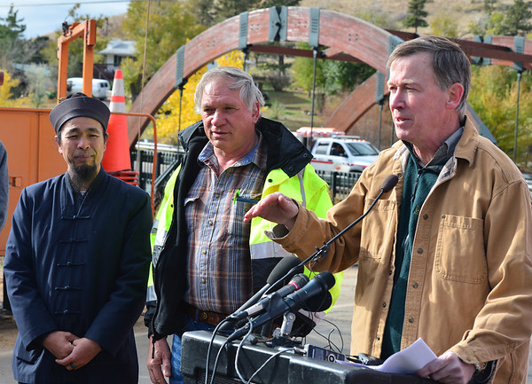 Colorado Governor John Hickenlooper, right, noted the efforts of Aspen Lodge owner Yun Xiang Tseng and heavy equipment operator Dan Crane who battled mudslides during the September flooding to minimize damage to Hwy. 7 to the south of Estes Park. Prior to Monday's reopening of Hwy. 36, this was the only road into Estes Park.