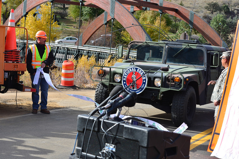 A Colorado National Guard Humvee breaks the barrier during ribbon cutting ceremonies Monday mornding signifying the reopening of Hwy. 36 between Estes Park and Lyons. The ceremony took place near Lyons.