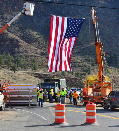 A large American flag was suspended over the ceremony site where officials gathered Nov. 4 near Lyons to mark the reopening of Hwy. 36 to Estes Park.