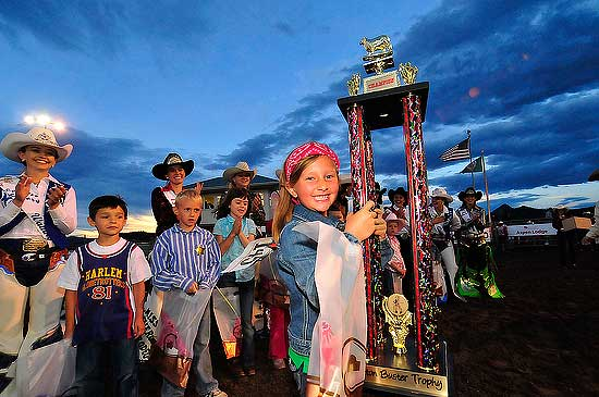 Kristen McCrea, 7, of Estes Park, smiles widely as she holds her mutton busting trophy on Saturday. Photo by Walt Hester.