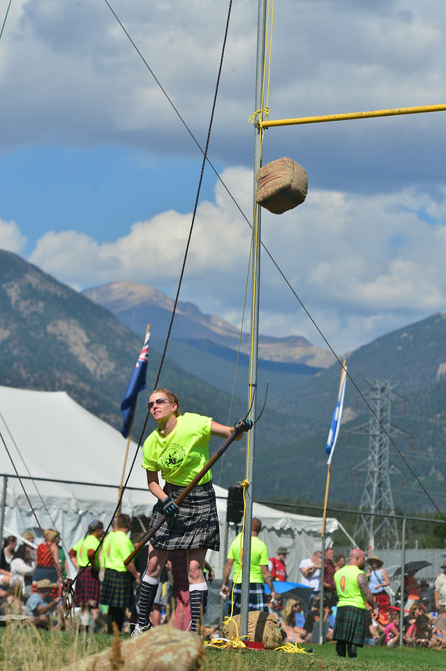 A female Highland athlete tosses a sheaf up and behind her on Sunday. As was the weather theme this year, the games began sunny and warm, but clouds were never far off and rain again deluged the field in the afternoon.