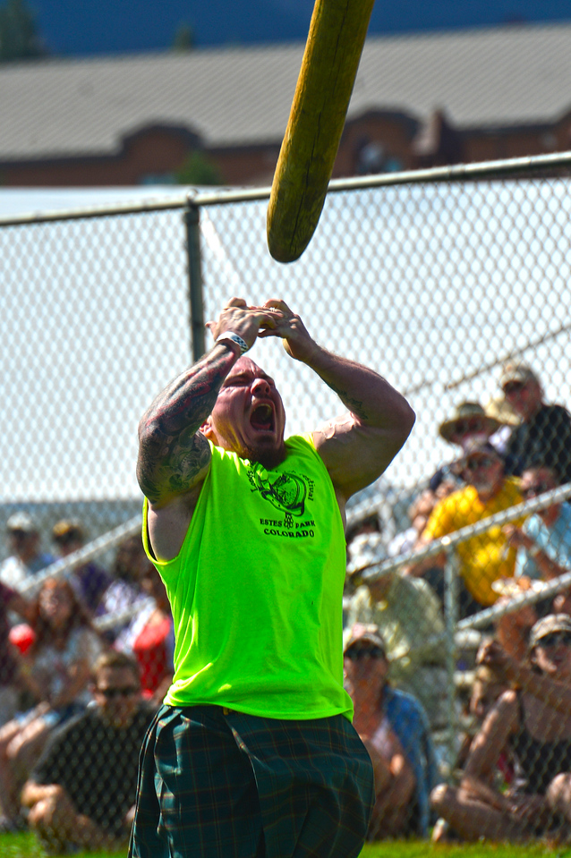A muscular Highland Games athlete tosses a caber on Sunday. The games were broken down into professional and several amature groups, including a sub-190-pound athlete group for men, and a women's open group.