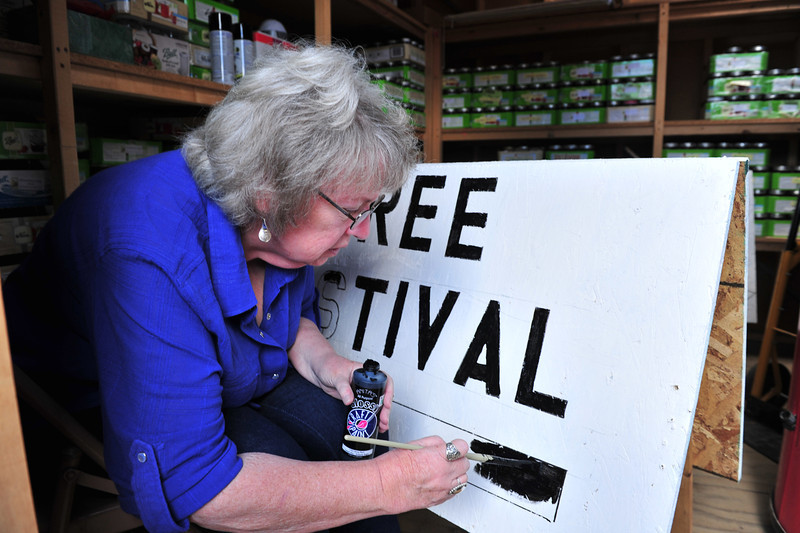 Vickie Dyas, co-chair of the Hilltop Guild Festival and Bazaar, paints a sign for the event. The annual fund raiser takes place at the Kelley House, 18720 Hwy 7, a few miles east of Allenspark, on Saturday, August 3, starting at 9 a.m.
