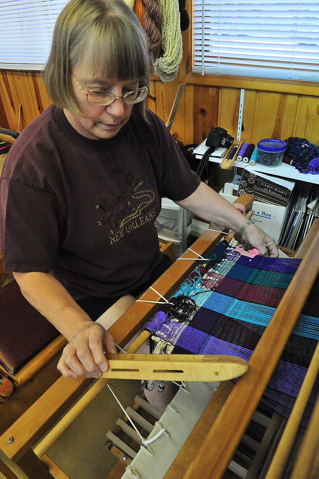 A weaver at the Hilltop Guild works on a rug on Wednesday. Much of what is sold at the guild's bazaar and festival is homemade.