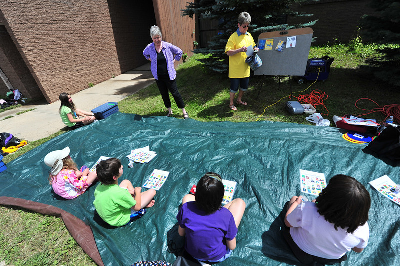 "Children sit and play ""book-cover bingo"" in Saturday's sunshine."