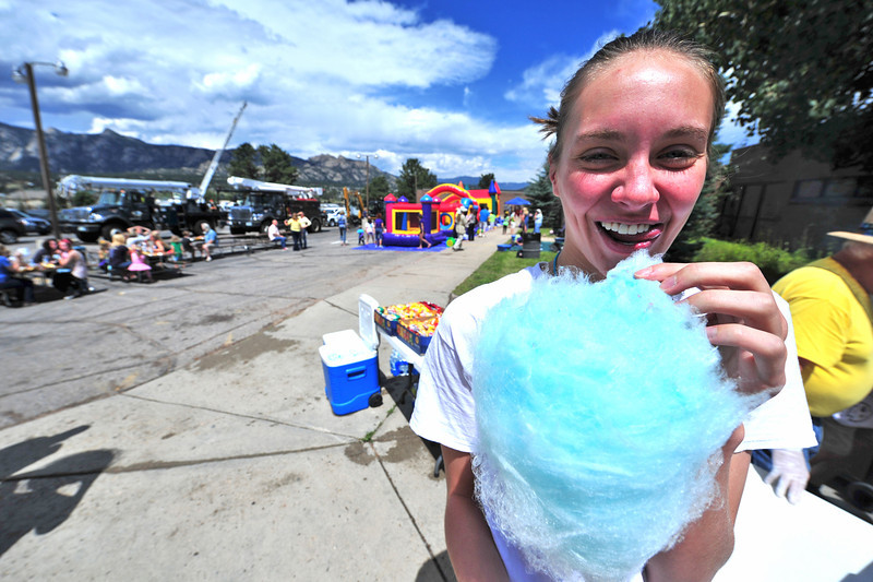 Lifeguard Emma Reins enjoys a littlesweet indulgence during Saturday's Back to School Bash at the Aquatic Center. The event featured big trucks, book cover bingo, bounce houses and goodies.