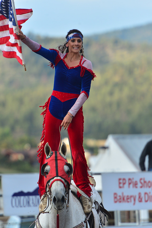 Brandy Phillips of Three Rivers, Calif., flies Old Glory during Tuesday's pre-rodeo show. Brandy is one of the veterans among the girls.