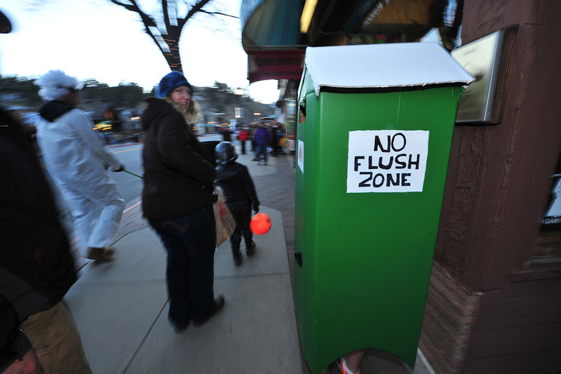 A child dressed as the now-familiar outhouses wanders up Elkhorn Avenue on Thursday. Many costumes made light of recent events and circumstances in Estes Park