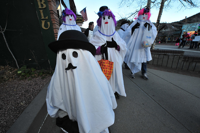 A family of ghosts float down Elkhorn Avenue on Thursday. Candy companies ca,e to the rescue for the annual event, donating several-thousand pounds of sweets for area ghouls and goblins, as well as princesses and pirates.