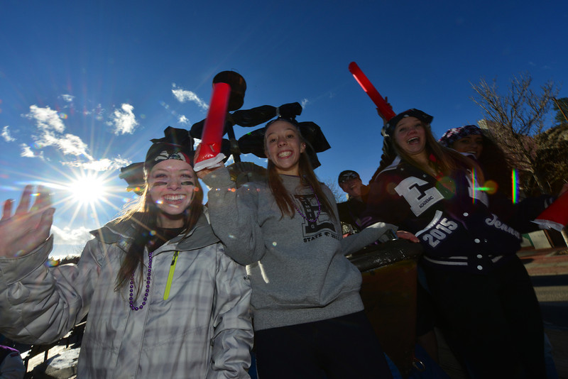Juniors wave inflatable sabers in the bright, autumnal sunshine on Friday. The juniors decorated a pirate ship-themed float for Friday's Homecoming parade.