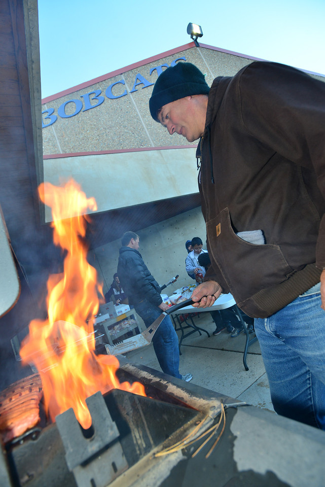Parents man the grill at the Homecoming tailgate party before the big game on Friday.