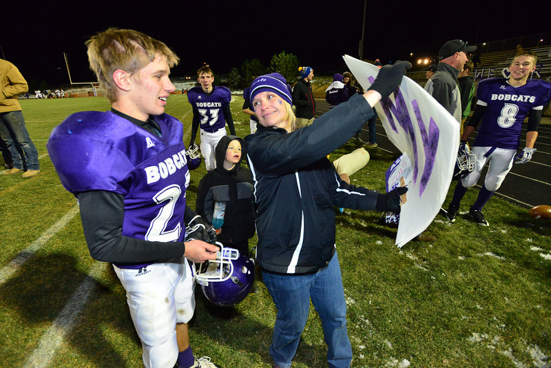 Junior Logan Ash enjoys a sign made by his proud mom after Friday's Homecoming game win. Ash scored the final touchdown in the Bobcats' 28-12 win over Nederland.