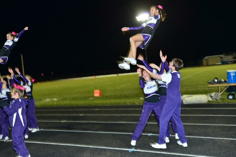 Estes Park cheerleaders flip and fly between the action of Friday's Homecoming football game.