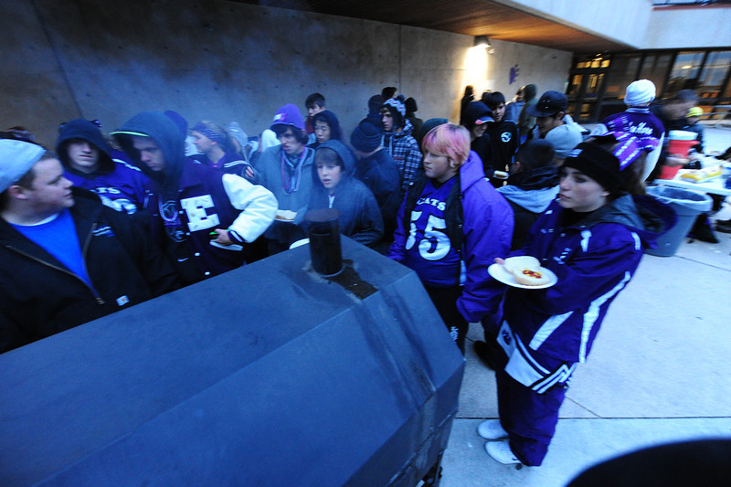 Perents and fans huddle around the grill during last year's pre-game tailgate party. The event is again scheduled for this year, starting at about 5:30 p.m., between the end of the parade and the kickoff of the game.