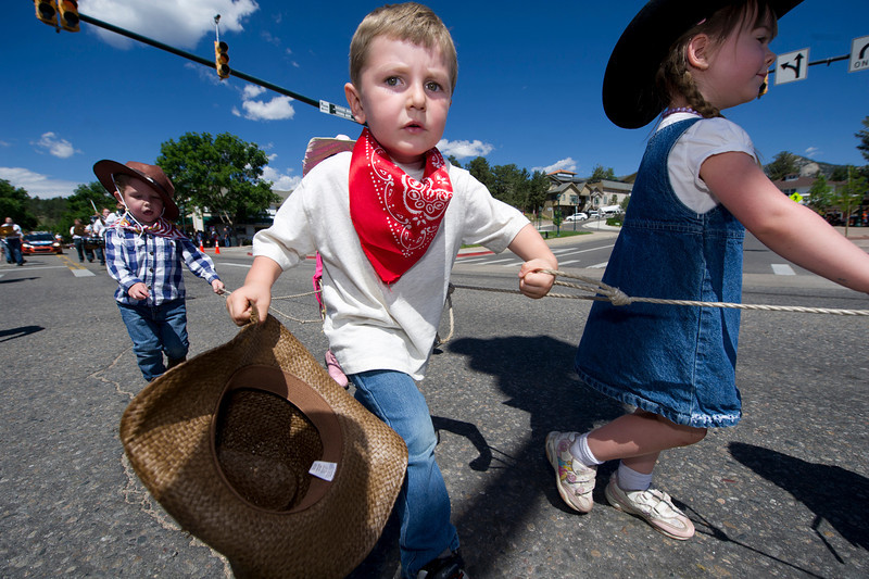 Little buckaroos from the Mountain Top Preschool hold on through the Rooftop Rodeo Parade on Tuesday. Participants walk more than a mile fromthe west end of Elkhorn Avenue to nearly the fairgrounds, well past the east end of downtown.