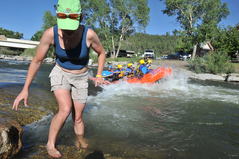 Amteur racer and RTide the Rockies participant Lanier Allen of Littleton backs into the chilly San Juan River as rafters splash through. Much of Pagosa Springs' economy is built around recreational tourists and those who visit for Pah Gosah, healing waters in the Ute language.