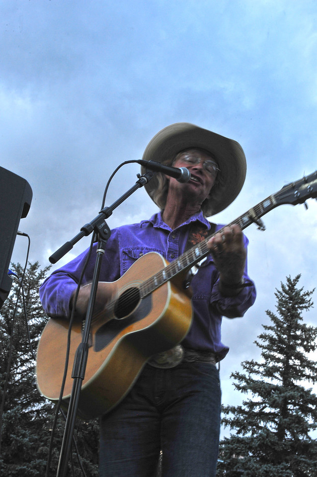 Cowboy Brad Fitch sings against the backdrop of fading evening light in Bond Park on Monday. The local singer-songwriter will be performing for a few more weeks in the park, as summer winds down.