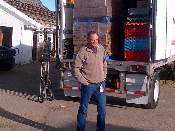 Keith Pearson, division president of McLane Western, stands behind the truck containing 141,000 pieces of candy donated by his company and his candy manufacturer partners.