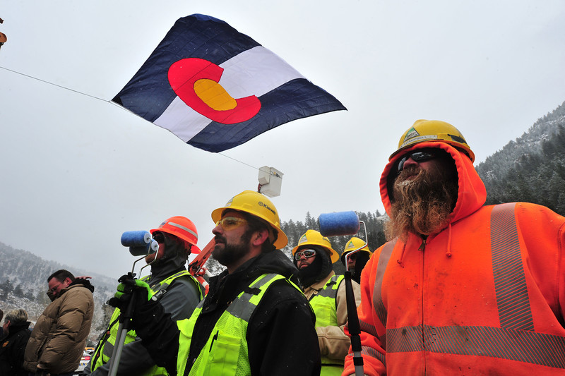 Workers from Kiewit Construction wait with paint rollers at the re-opening ceremony for US Hwy 34 at the Drake Fire Station on Thursday. Colorado's governor, along with mayors from Estes Park and Loveland, painted the last section of yellow striping on the highway.