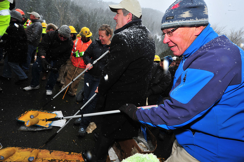 Estes Park Mayor Bill Pinkham helps paint the last bit of yellowstripe on US Hwy 34 in Drake on Thursday. Officials from Estes Park traveled to Drake for the official re-opening ceremony for US Hwy 34.