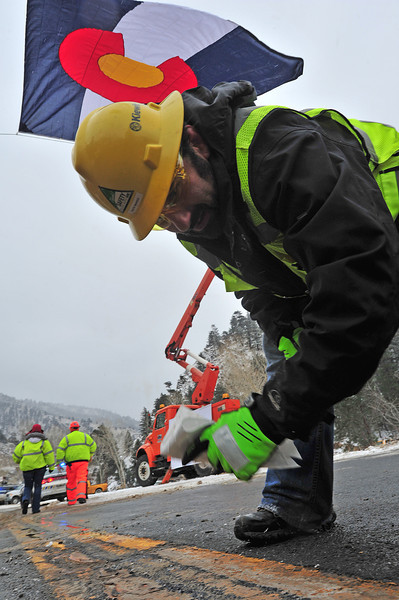 Nate Mares of Kiewit Construction wipes off a spot on US Hwy 34 that needs paint amid Thursday's snow. Kiewit, CDOT and the Army Corps of Engineers worked 24 hours a day, six days a week and a half day on Sundays to get the major artery between Loveland and Estes Park open 10 days early.
