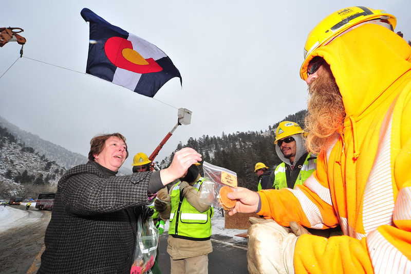 Susan Albern of Cidar Cove hands out homemade cookies to Kiewit Construction workers before the ceremony officially re-opening US Hwy 34 on Thursday. Crews finished the temporary road 10 days ahead of schedule.