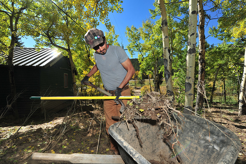 Javier Garza of San Antonio, Texas cleans debris from behind guest cabins at Aspin Lodge on Tuesday. The Twin Sisters mud slide deposited branches, rocks and, of course, mud all over the lodge's property.