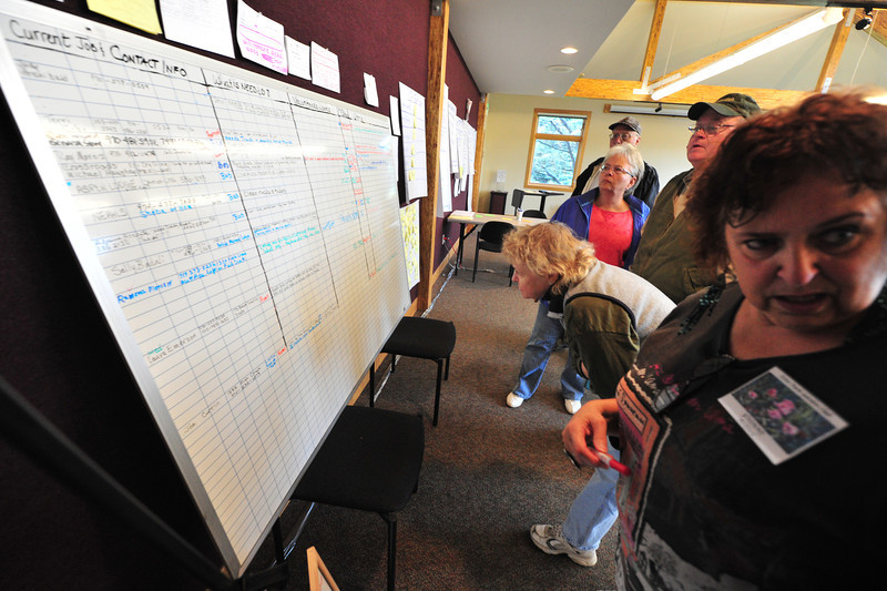 volunteers check a big board at the Estes Park History Museum on Monday to find clean-up projects in need of volunteer help. The Volunteer Clearing House receives requests, then tries to match volunteers to projects.