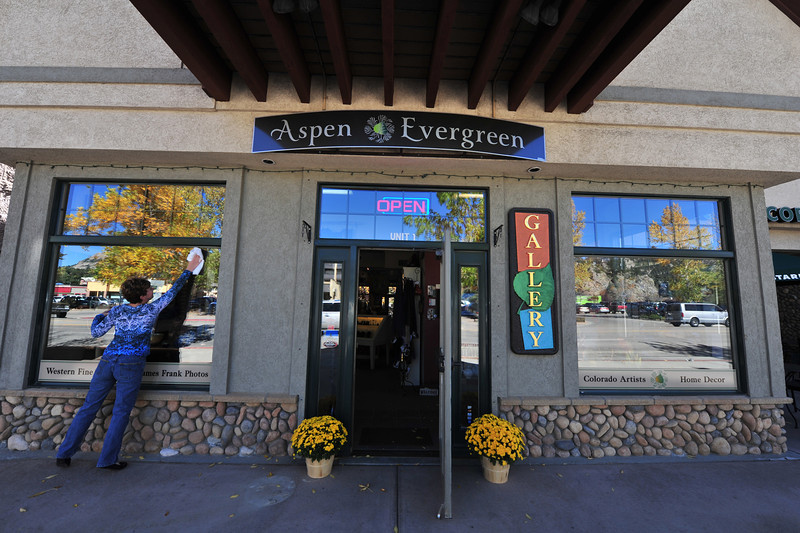 Tamara Jarolimek cleans windows of the Aspen and Evergreen gallery on Monday. The gallery sat just enough higher than its neighbors to limit water damage.