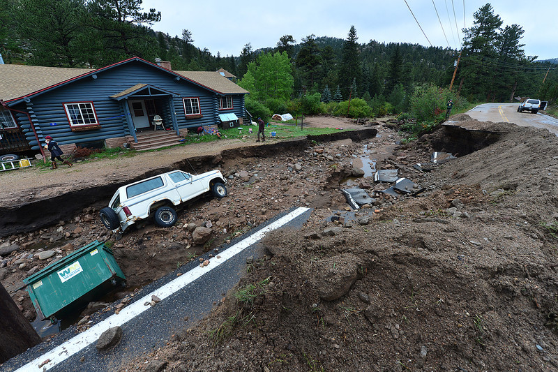 A dumpster and an SUV rest in a gully above Glen Haven formed by last week's flood. Roads, property and lives were lost in the single largest flood event in the state's history.
