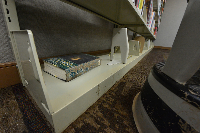 One book shows mud from last week's flood in the Estes Valley Public Library on Saturday. The library suffered only minor damage to carpets and a very few books.