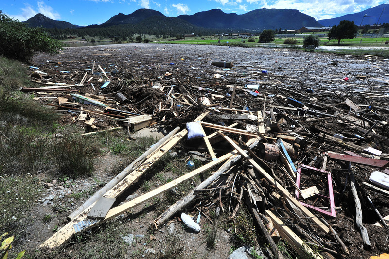 Piles of refuse clog the south side of Lake Estes on Monday. The pile includes matresses, bottles, coolers, pieces of homes and human waste.