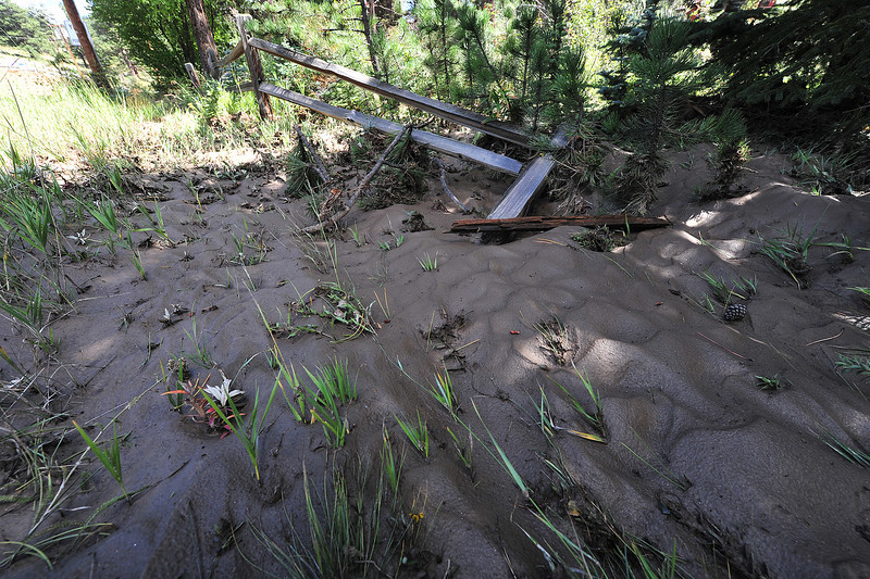 Waves of mud and grass show the path of floodwaters along the Fall River on Tuesday. As waters recede, the damage is revealed in the Estes Park area.
