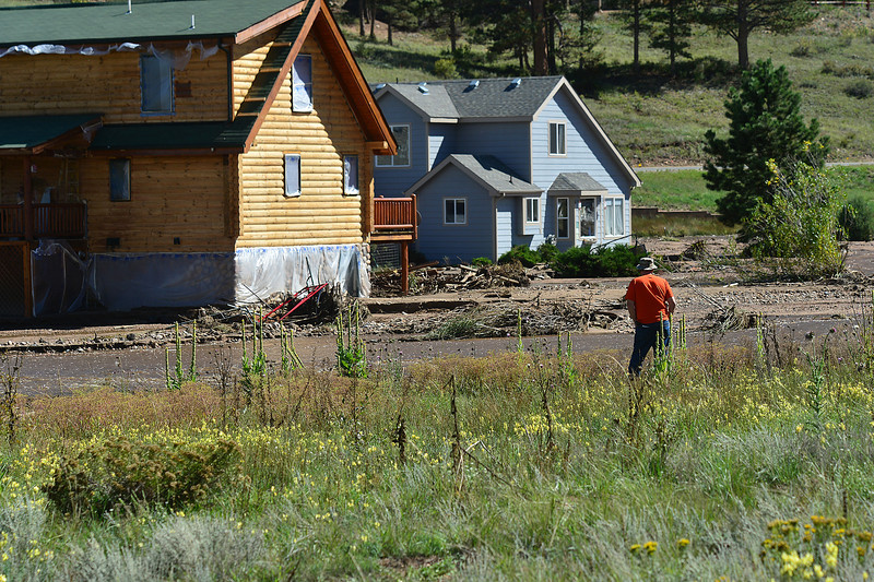 Retired Chicago area police detective and Estes Park resident Joseph Curtin admires his sturdy home, right, on Tuesday. Curtin's home was surrounded by flood waters of the Fish Creek at the hight of last week's storm.