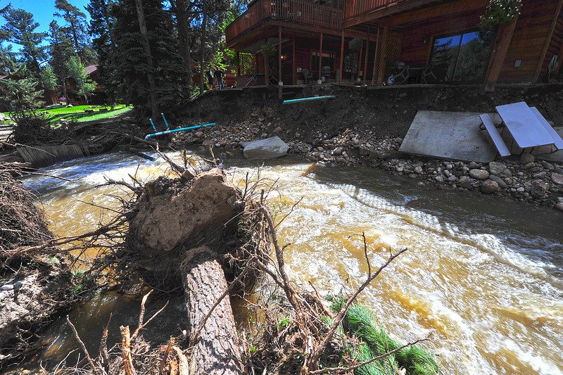 Uprooted trees, concrete slabs, plumbing and more clog the Fall River near Fish Hatchery Road on Tuesday. Many lodges and hotels along the road were damaged or isolated by last week's flood.