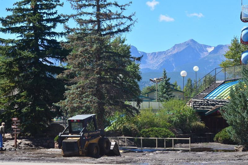 A mini excavator pushes mud off of the Fun City parking lot on Tuesday. Estes Park is starting the long process of recovery, cleaning up and assessing damage.