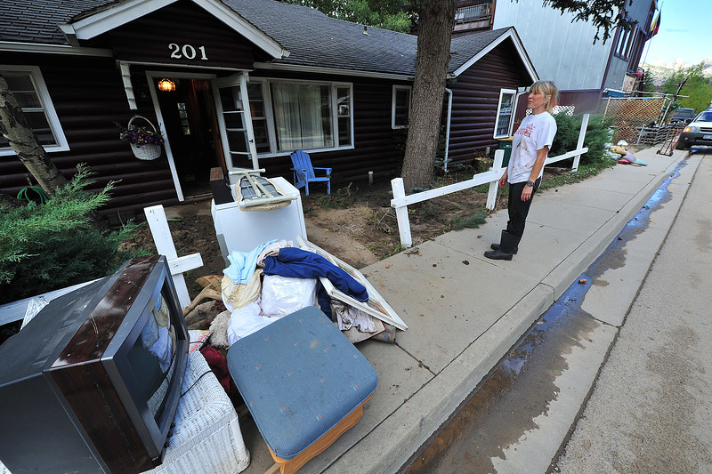 Mary K. Somin watches as her house on East Riverside Drive is emptied on Wednesday. Like many in Estes Park, Simon has to take out wet and ruined items before trying to dry out the building, itself.