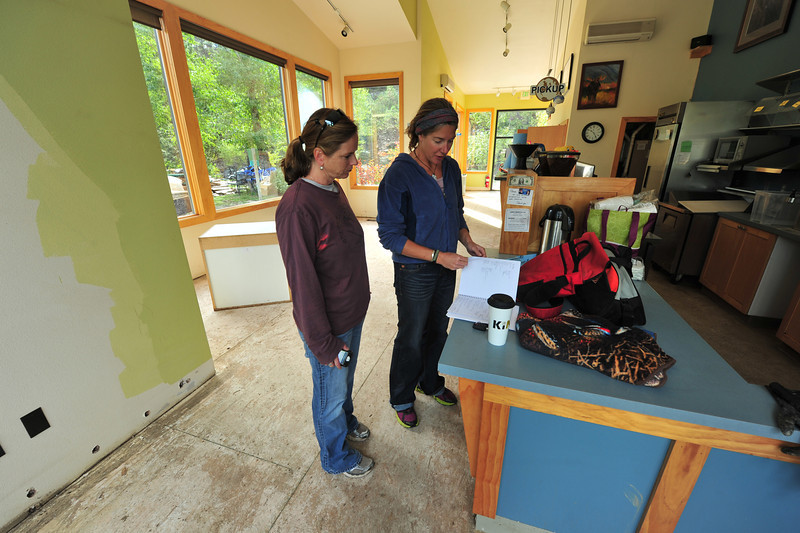 Kind Coffee owner Amy Hamrick and Teresa Flicek look through Hamrick's book of people who have helped clean up the coffee shop after the flooding. Twenty-five percent of sales of Kind Coffee's new blend will go to the Town of Estes Park Flood Releaf Fund, started by Susie Masterson of the Winter Park Chamber of Commerce.