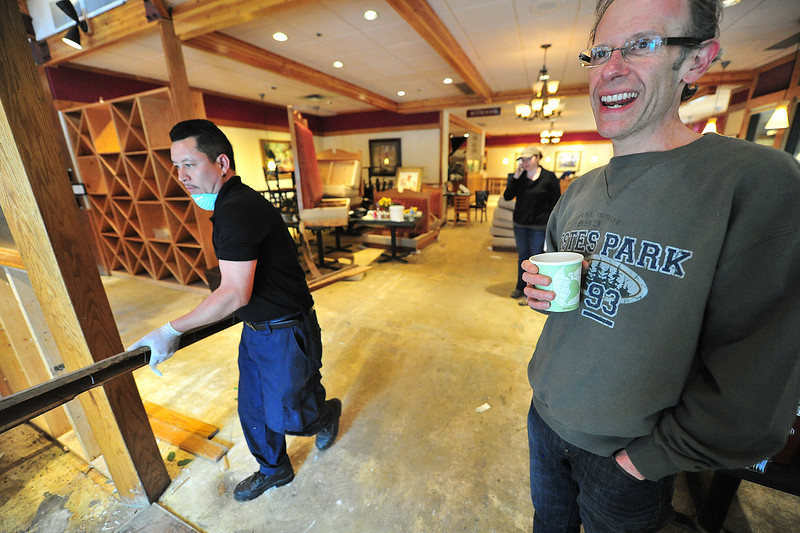 Poppy's co-owner Rob Pieper takes a break while employees help remove damaged items from the restaurant. Pieper sees several weeks of repair ahead before reopening.