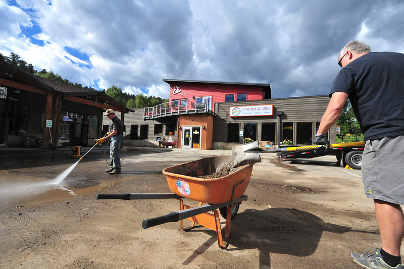Estes Park business owners and others scoop  and blast mud from a parking lot on East Elkhorn Avenue on Wednesday. While some worry about applying more water to town streets and lots, businesses want to clean up before visitors return to Estes Park.